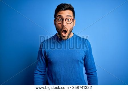 Young handsome man with beard wearing casual sweater and glasses over blue background afraid and shocked with surprise and amazed expression, fear and excited face.