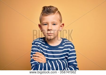 Young little caucasian kid with blue eyes wearing nautical striped shirt over yellow background skeptic and nervous, disapproving expression on face with crossed arms. Negative person.