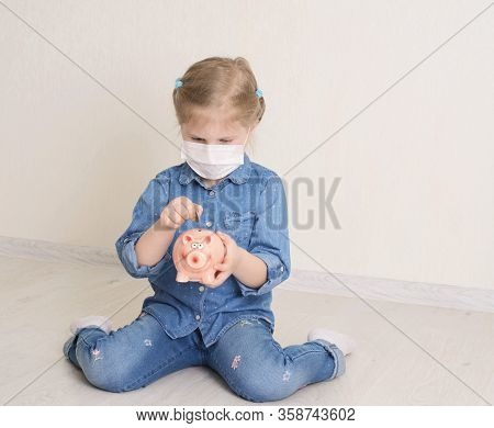 Sad Child Girl In Protective Medicine Mask Holding Piggy Bank. Saving Money Concept. Little Girl Put