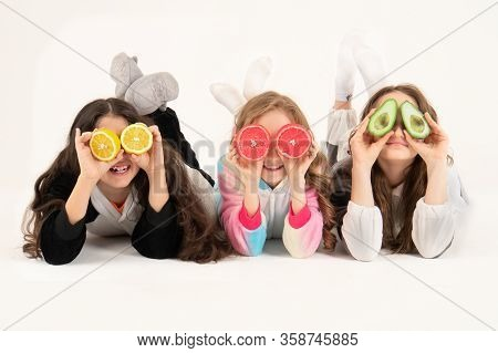 Three Girls Using Fruits As Glasses On A On A White Background. Group Of Happy Children With Grapefr