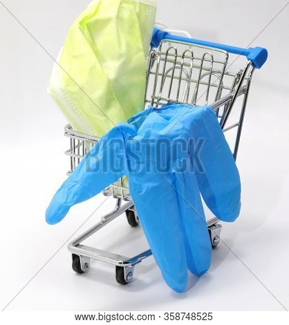 Very Small Shopping Trolley With Protective Latex Glove And Surgical Mask On White Background