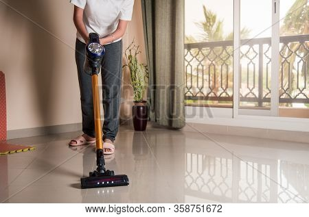 Woman Vacuuming The Living Room Floor With Cordless Vacuum Cleaner