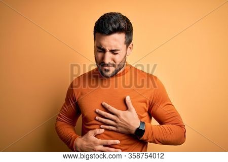 Young handsome man with beard wearing casual sweater standing over yellow background with hand on stomach because indigestion, painful illness feeling unwell. Ache concept.