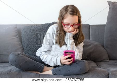 Bored Girl Sitting On The Couch And Holding A Mobile Phone.boredom In Home Sandbox. While It`s Not A