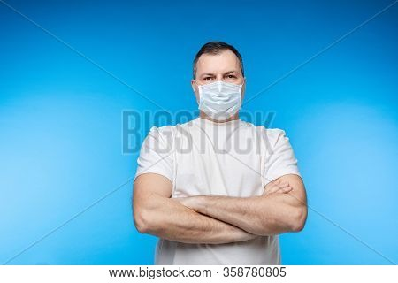 Man In Aseptic Mask With Folded Arms.