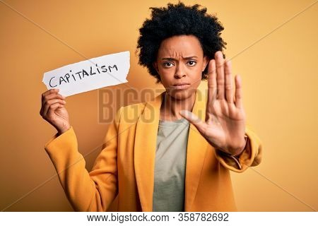 African American afro businesswoman with curly hair holding paper with capitalism message with open hand doing stop sign with serious and confident expression, defense gesture