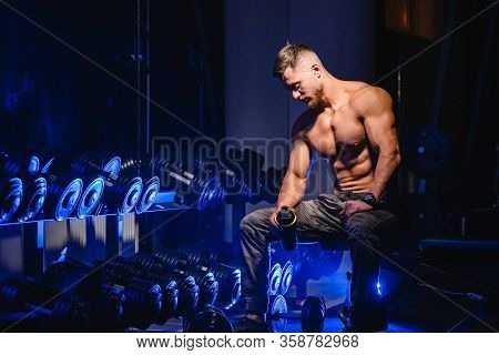 Handsome Man With Big Muscles, Posing At The Camera In The Gym, Black And Blue Background. Portrait