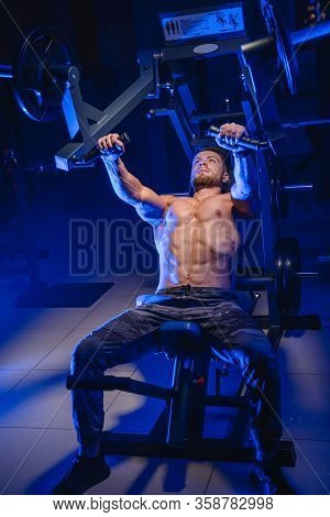 Athletic Man In Gym Exercising On The Barbell Bench Press. Bodybuilder With Perfect Body. Blue Filte