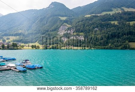 View Over The Lake Lungern. Lungernsee Is A Natural Lake In Obwalden. Wooden Pier With Boats. Beauti
