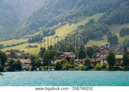 View Over The Lake At With Mountains In The Background. Houses On The Shore Of A Picturesque Lake