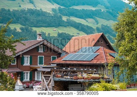 Solar Panel On A Red Roof Of A Building. Green Energy.