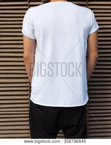 Fashion Street Youth. A Man In A White T-shirt Posing With His Back To The Camera On A Dark Blue Met