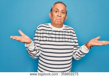 Senior handsome grey-haired man wearing striped sweater over isolated blue background clueless and confused expression with arms and hands raised. Doubt concept.