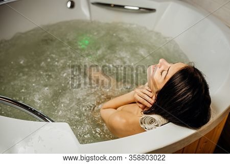 Woman Relaxing At Home In The Hot Tub Bath Ritual.spa Day Moment In Modern Bathroom Indoors Jacuzzi