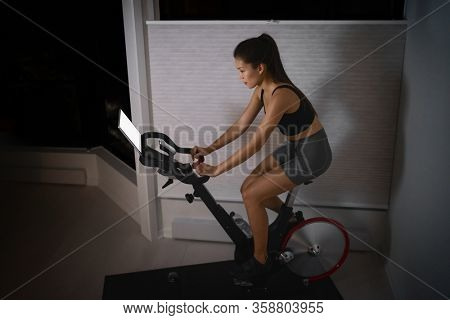 Home workout indoor stationary bike Asian girl biking screen with online classes woman training on smart fitness equipment indoors for cycling exercise. Late at night in bedroom.