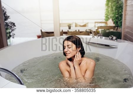 Woman Having A Spa Day  Moment In Modern Bathroom Indoors.relaxing At Home In The Hot Tub Bath.indoo