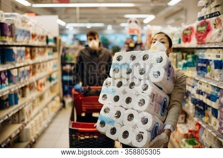 Woman Couple With Mask And Gloves Panic Buying And Hoarding Toilette Paper In Supply Store.pathogen