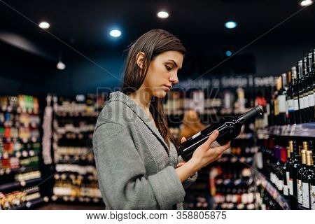 Woman Shopping For Expensive Wine In Supermarket Alcohol Store.choosing And Buying Good Cheap Wine.b