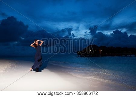 Fashion woman in dress walk on the beach sunset background. Happy lifestyle. White sand, dawn cloudy sky and blue sea of tropical beach