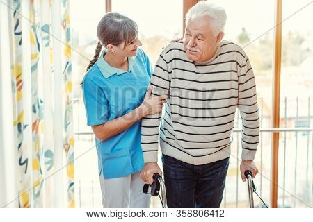 Smiling nurse helping senior man with walking frame in the nursing home