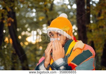 Sneezing Guy With Handkerchief In Autumn Park. Sick Man Trying To Sneeze In The Napkin. Stop The Flu