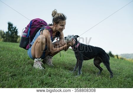 Happy Young Woman With Backpack Kneeling Down On Green Meadow To Pat Her Black Dog As They Go On A H