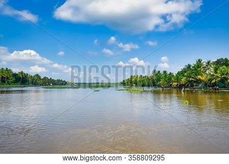 Beautiful View Of Backwaters In Kerala, India With Vegetation And Coconut Trees On The Banks And A C