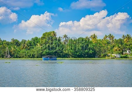 A Small Blue Passenger Boat In The Backwaters Of Kerala, India With Thick Green Vegetation And A Cle
