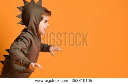 Little Brunet Model In Brown Dino Hoodie With Hood. He Is Roaring And Scaring You, Posing Sideways A