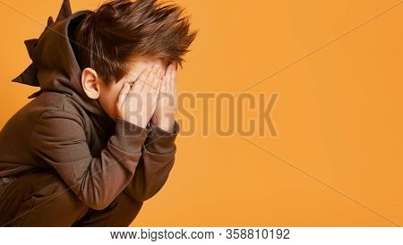 Little Brunet Child In Brown Dino Hoodie With Hood. He Has Covered His Face With Palms, Posing Sitti