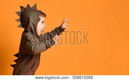 Little Brunet Male In Brown Dino Hoodie With Hood. He Is Growling And Scaring You, Posing Sideways A