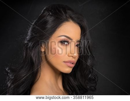 Beautiful young woman's face with gorgeous curly black hair