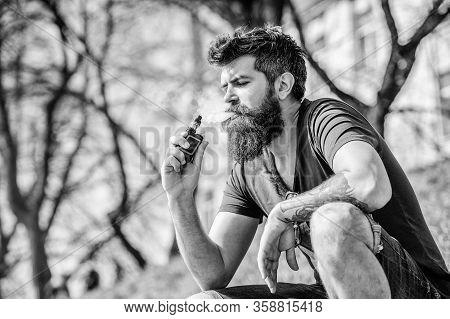 Smoking Device. Man Long Beard Relaxed With Smoking Habit. Man With Beard Breathe Out Smoke. Clouds