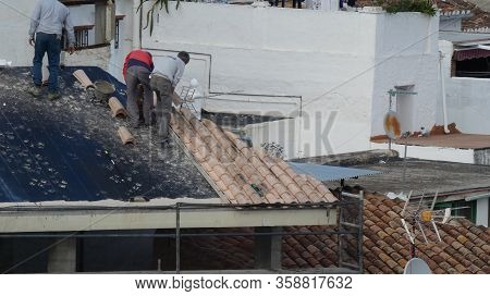 Alora, Spain - December 18, 2019: Workers Laying Traditional Roof Tiles On Village House
