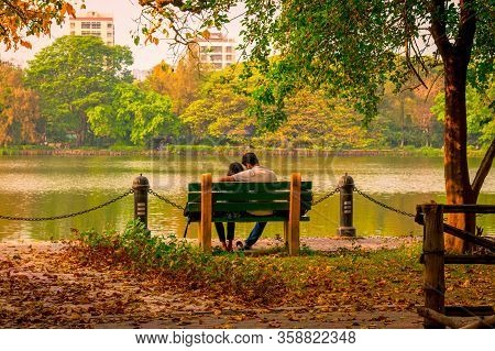 Young Couple Sitting In An Autumn Park Bench In Lakeshore. Falling In Love In Maple Leaf Garden. Rel
