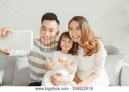 Family Clicking Selfies While Sitting On Sofa At Home