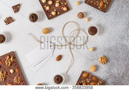 Homemade Milk Chocolate Bars And Pralines With Dried Berries And Nuts On Light Background. Top View.