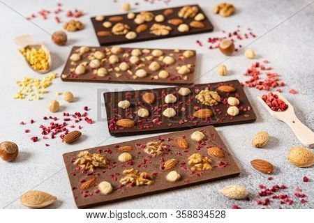Homemade Milk And Dark Chocolate Bars With Dried Berries And Nuts On Light Background. Side View. Ch