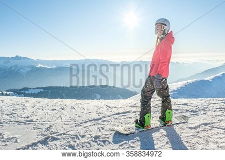 Back View Of Female Snowboarder Standing With Snowboard And Enjoying Mountain Landscape. Snowboardin