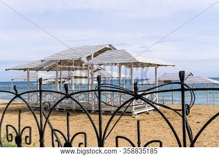 Wooden Sunshade Is On Deserted Sandy Beach On Sea Coast. View Through Fence. Sunny Day