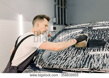 Car Wash And Clean With Shampoo And Sponge. Young Handsome Man Worker Washing Soapy Car Windshield W