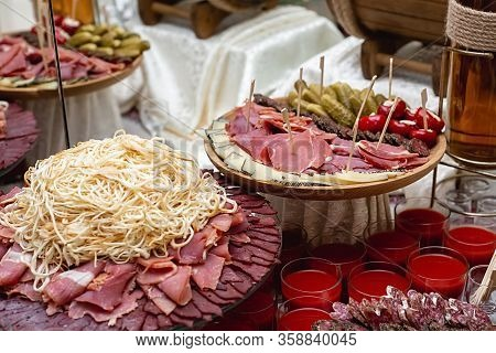 Cheese, Cold Meats, Sliced Sausages, Cucumbers, Tomatoes And Fresh Red Juice On A Festive Table. Var