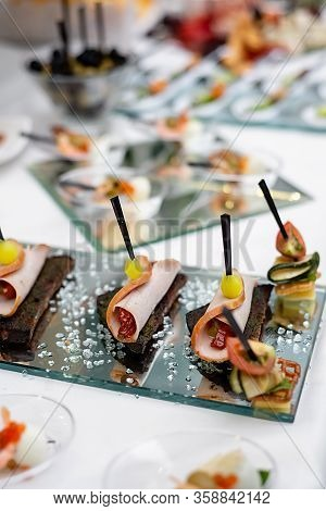 Variety Of Tasty Delicious Snacks. Close Up Of Sliced Meat On Bread On A Glass Table. Delicious Snac