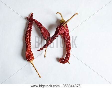 Letter M Lined With Red Peppers On A White Background. Symbol In The Form Of The Letter M. Pepper Li