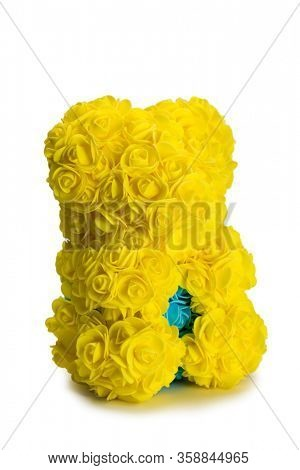 Artificial bouquet of yellow flowers in the shape of a bear. Isolated on white.