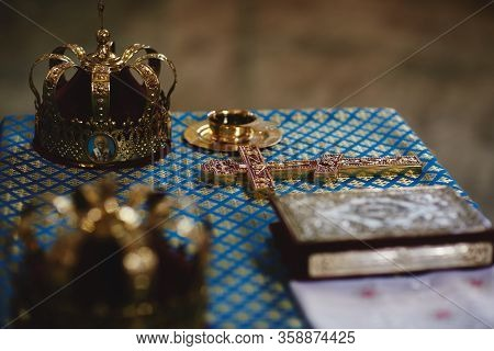 Orthodox Golden Wedding Crowns, Church Icons, Church Books, Gospel On The Table. Selective Focus