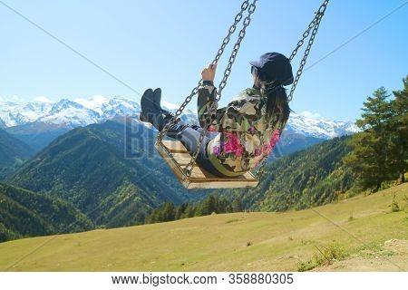 Female Trekker On The Mountain Swing With Stunning View Of Caucasus Mountain In Mestia, Svaneti Regi