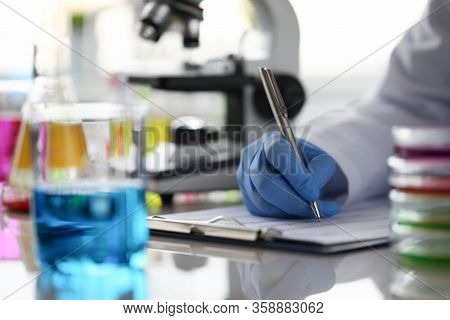 Close-up Of Researcher Hand Holding Pen. Woman Writing Results Of Experiment In Documents. Scientist