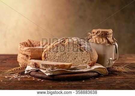 Cut Loaf Of Artisanal Wheat Bread In A Wooden Background