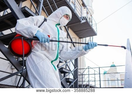 Coronavirus Pandemic. A Disinfector In A Protective Suit And Mask Sprays Disinfectants In House Or O